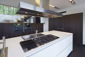 Kuchyňská linka v kombinaci tmavě mořený dub, nerez a Corian, vytváří dokonale sladěný a funkční celek.